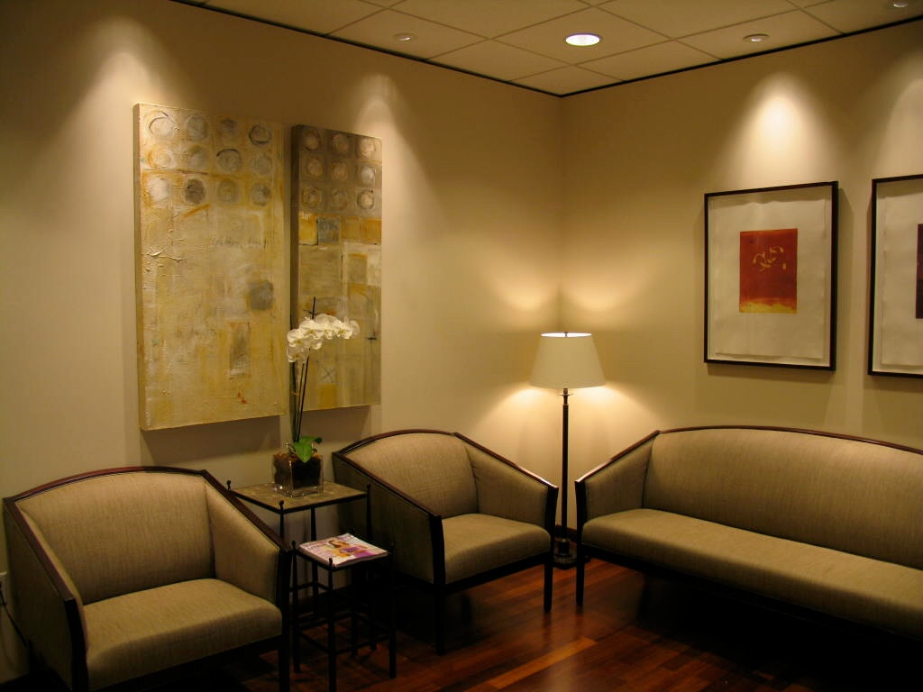 Houston Dermatology waiting room with two chairs and a couch, lamp and pictures on the wall.