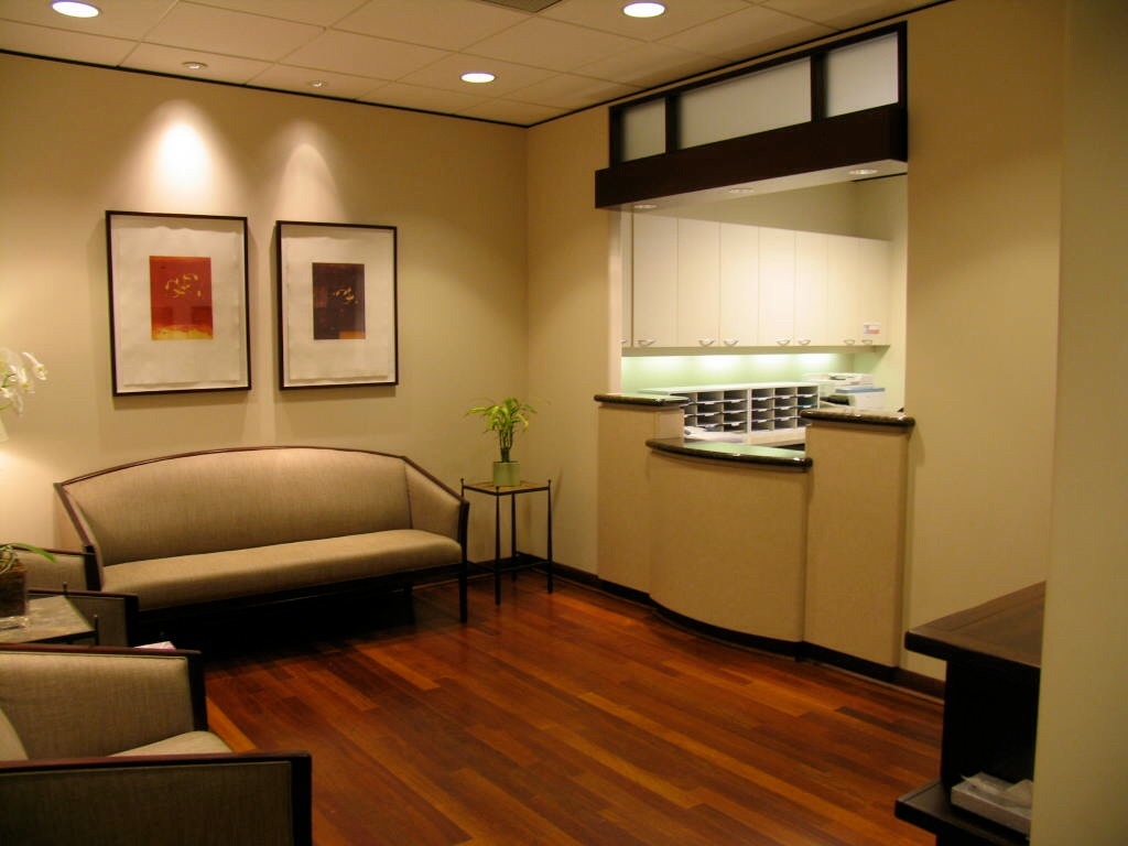 Our Houston dermatology waiting room with beige couches, two pictures above the couch and the reception desk.